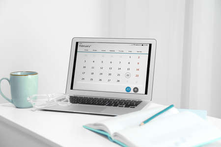 Modern laptop with calendar on screen in office Stock fotó