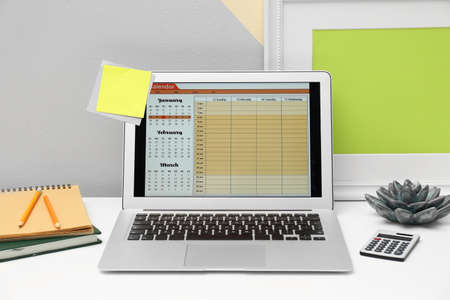 Modern laptop with calendar on screen in office