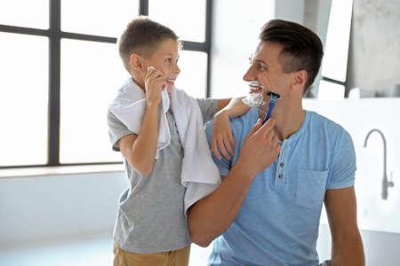 Figlio che si pulisce la faccia con un asciugamano mentre suo padre si fa la barba in bagno Archivio Fotografico