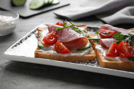 Tasty sandwiches with ham served on grey table, closeup