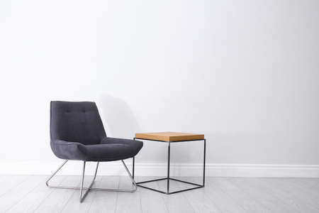 Comfortable armchair and table near light wall. Space for text