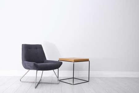 Wygodny fotel i stolik przy jasnej ścianie. Miejsce na tekst