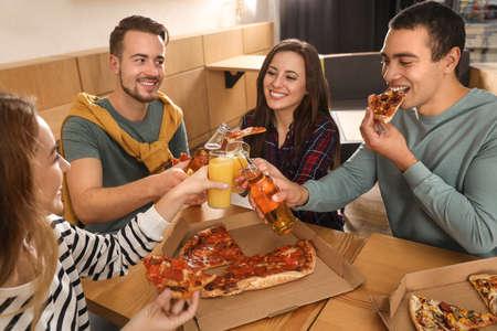 Gruppe von Freunden, die eine lustige Party mit köstlicher Pizza im Café haben Standard-Bild