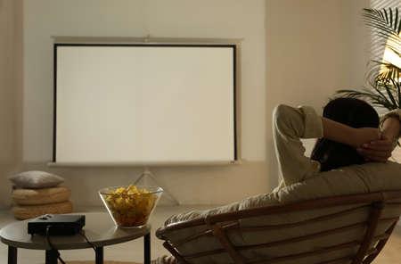 Mujer joven viendo una película con proyector de vídeo en casa