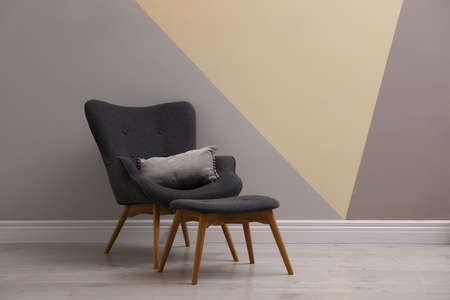Comfortable armchair with cushion and footstool indoors