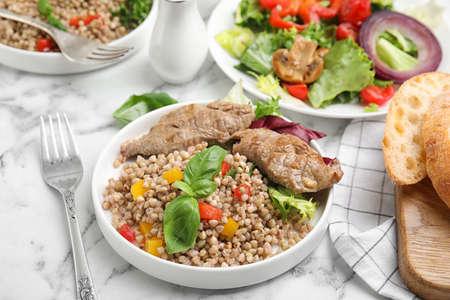 Tasty buckwheat porridge with meat on white marble table Stock Photo