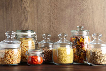 Glass jars with different types of groats and pasta on wooden table Foto de archivo