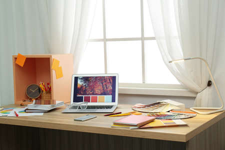 Designer's workplace with modern laptop and color palettes