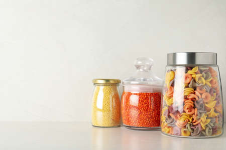 Glass jars with different types of groats on white wooden table