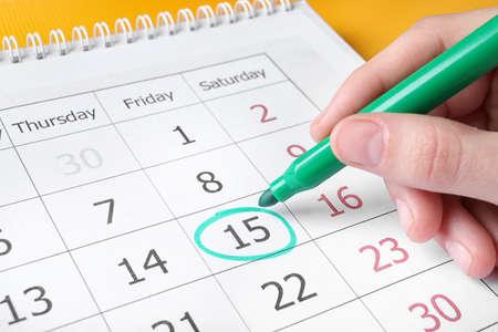 Woman marking date in calendar with felt pen, closeup