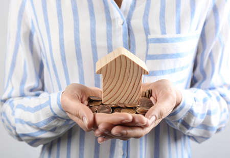 Woman holding coins and house model, closeup