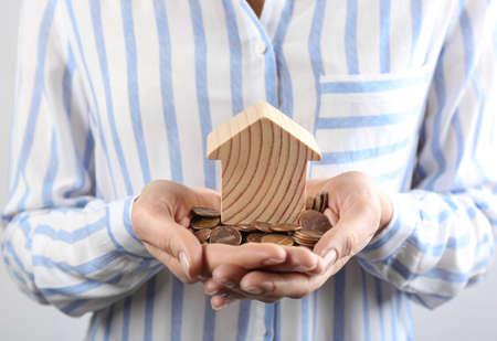 Femme tenant des pièces et modèle de maison, gros plan Banque d'images