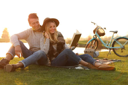 Happy young couple reading book while having picnic outdoors 版權商用圖片