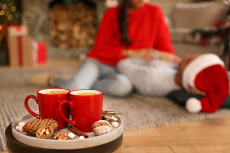 Happy couple on floor in room, focus on tray with cups. Christmas celebration