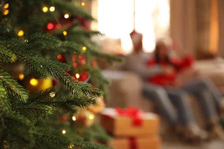Couple on sofa indoors, focus on Christmas tree Stock Photo