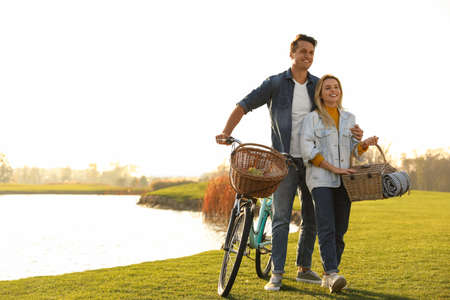 Young couple with bicycle and picnic basket near lake on sunny day