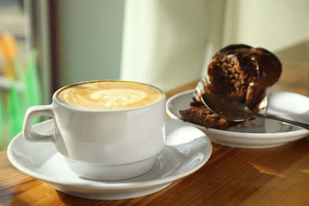 Cup of fresh aromatic coffee and cupcake at table in cafe
