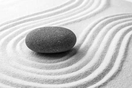 Grauer Stein auf Sand mit Muster. Zen, Meditation, Harmonie