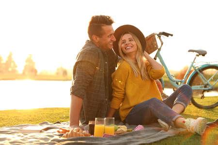 Felice giovane coppia che fa picnic all'aperto in una giornata di sole