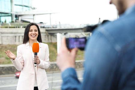 Joven periodista y operador de video que trabaja en las calles de la ciudad Foto de archivo