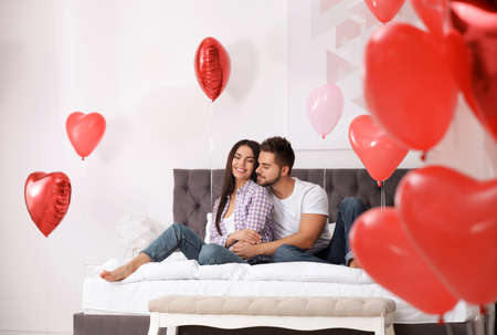 Lovely young couple in bedroom decorated with heart shaped balloons. Valentine's day celebration