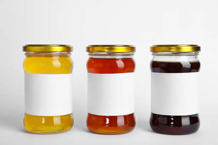 Different types of honey with blank labels isolated on white