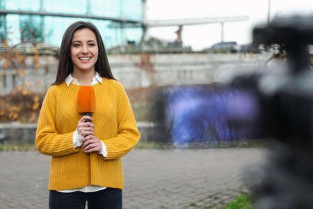Joven periodista con micrófono trabajando en las calles de la ciudad