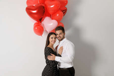 Happy young couple with heart shaped balloons on light background. Valentine's day celebration Stock fotó