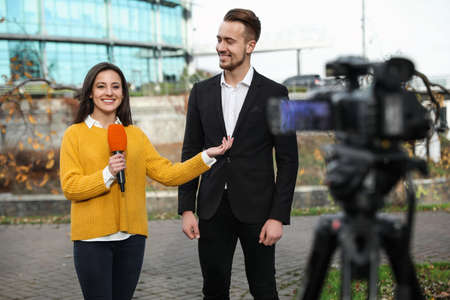 Young journalist interviewing businessman on city street