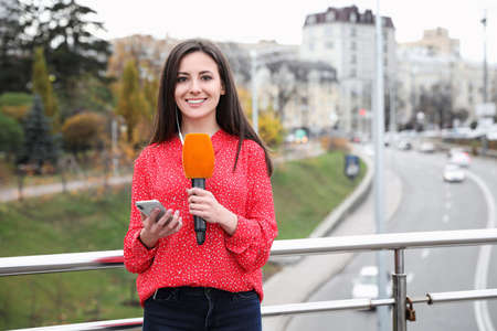 Young female journalist with microphone and smartphone working on city street. Space for text Imagens