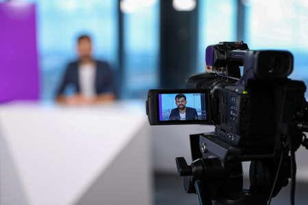 Presenter working in studio, focus on video camera Banque d'images