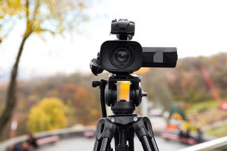 Video camera on tripod outdoors. Professional equipment