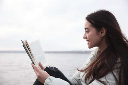 Woman reading book near river on cloudy day