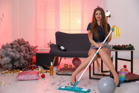 Woman with mop suffering from hangover in messy room after New Year party Reklamní fotografie