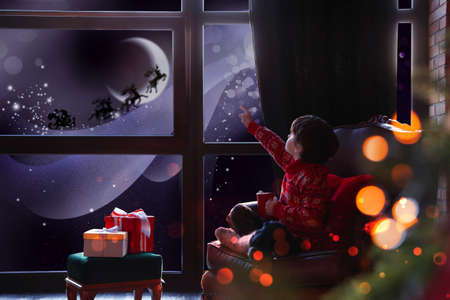 Cute little boy waiting for Santa Claus near window at home. Christmas holiday