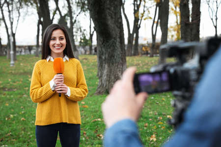 Young journalist and video operator working in park
