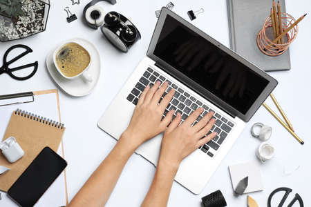 Female designer working with laptop at white table, top view