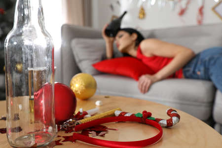 Young woman suffering from hangover  after New Year party, focus on messy table