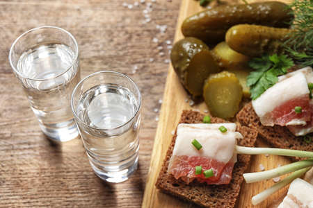 Cold Russian vodka with snacks on wooden table, above view