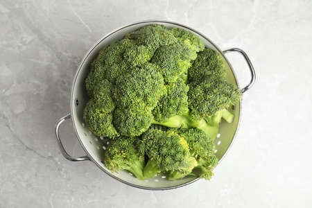 Fresh green broccoli in colander on grey marble table, top view