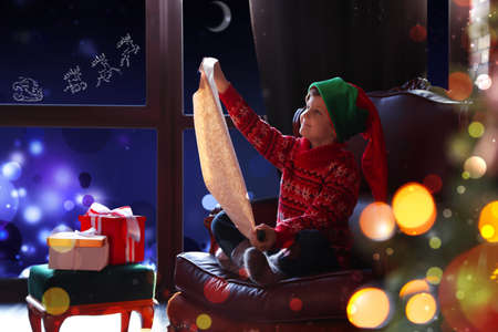 Cute little boy with wish list to Santa Claus near window at home. Christmas holiday
