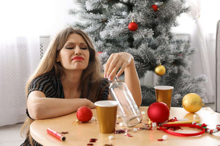 Young woman suffering from hangover at messy table after New Year party Reklamní fotografie