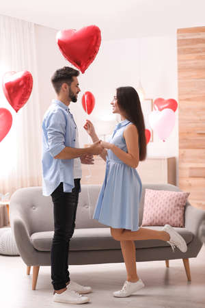 Happy young couple in living room decorated with heart shaped balloons. Valentine's day celebration
