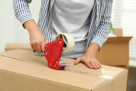 Woman packing cardboard box indoors, closeup. Moving day