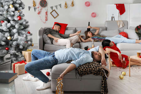 Friends suffering from hangover in messy room after New Year party