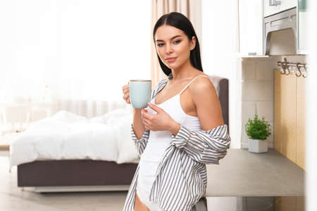 Beautiful young woman in white underwear drinking coffee at home Stock Photo