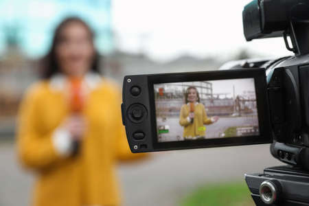 Young female journalist with microphone working on city street, focus on camera display