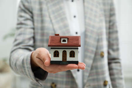 Real estate agent holding house model indoors, closeup