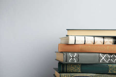 Collection of old books on light background, space for text