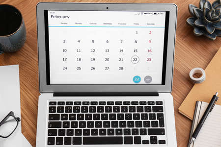 Modern laptop with calendar on wooden table, above view